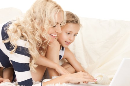 bright picture of happy mother and child with laptop computer (focus on woman) Stock Photo - 9545823