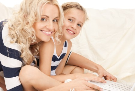 bright picture of happy mother and child with laptop computer (focus on woman) photo