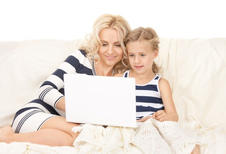 bright picture of happy mother and child with laptop computer