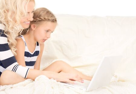 preteen girls: bright picture of happy mother and child with laptop computer Stock Photo