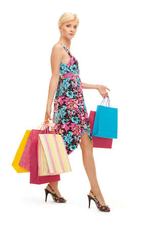 carrying girl: lovely woman with shopping bags over white