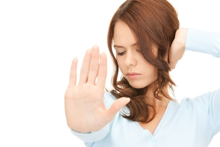 insult: bright picture of young woman making stop gesture Stock Photo