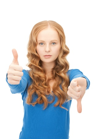 bright picture of lovely teenage girl with thumbs up and thumbs down  photo