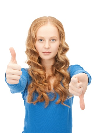 disapprove: bright picture of lovely teenage girl with thumbs up and thumbs down