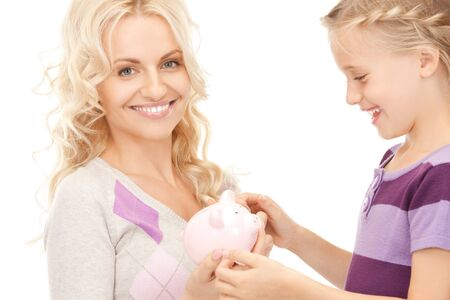 picture of mother and little girl with piggy bank (focus on woman) photo