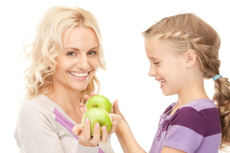 picture of mother and little girl with green apple (focus on girl) photo