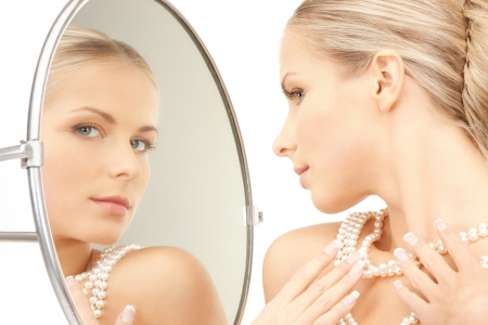 picture of beautiful woman with pearl beads and mirror photo