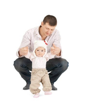 toddler walking: picture of baby making first steps with father help Stock Photo