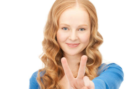 bright picture of lovely teenage girl showing victory sign photo