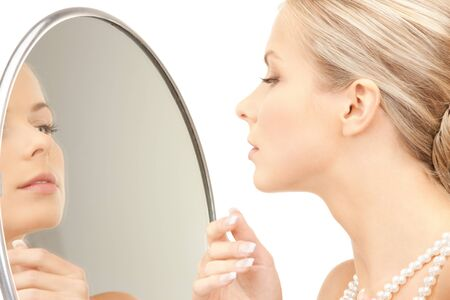 picture of beautiful woman with pearl beads and mirror. photo