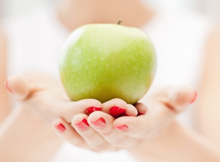 bright picture of female hands with green apple photo