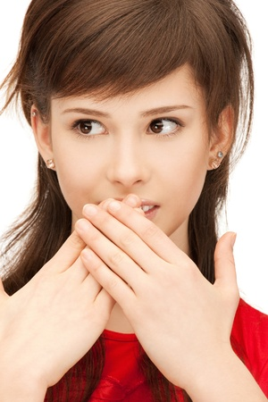 bright closeup portrait picture of teenage girl with palms over mouth photo
