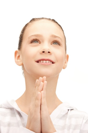 bright closeup portrait picture of praying teenage girl photo