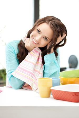 clean dishes: bright picture of lovely housewife at the kitchen