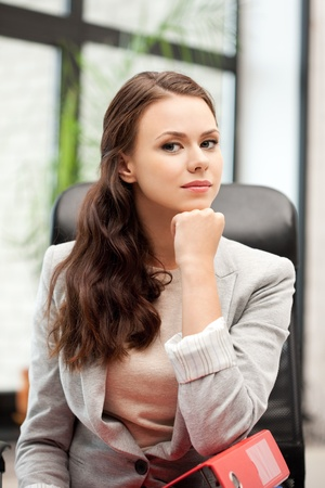 gorgeous businesswoman: picture of young businesswoman with folders sitting in chair