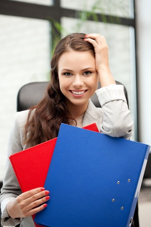 picture of young businesswoman with folders sitting in chair photo