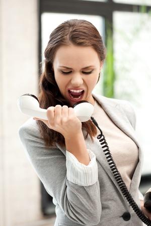 jefe enojado: imagen brillante de empresaria enojada con teléfono Foto de archivo