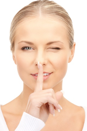 bright picture of young woman with finger on lips Stock Photo