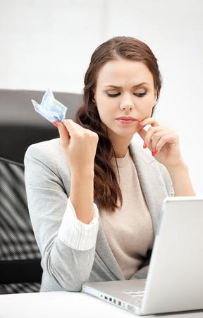 mujer pensativa: Foto de mujer pensativa con la computadora portátil y el dinero efectivo en euros Foto de archivo