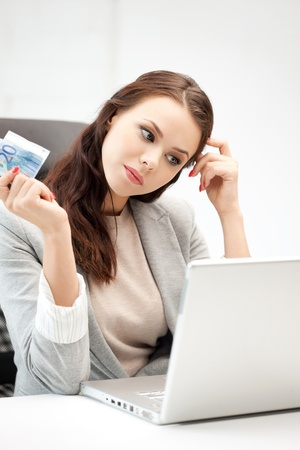 earn money online: picture of pensive woman with laptop computer and euro cash money Stock Photo