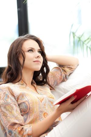 mujer leyendo libro: brillante imagen de mujer feliz y sonriente con un libro
