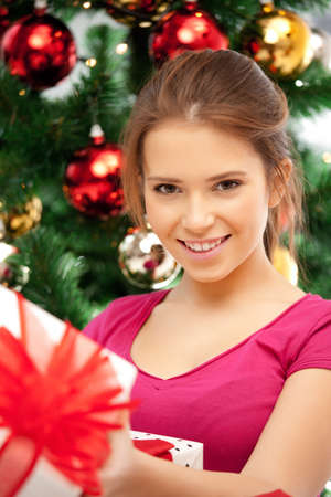 bright picture of happy woman with gift box and christmas tree Stock Photo - 21278376