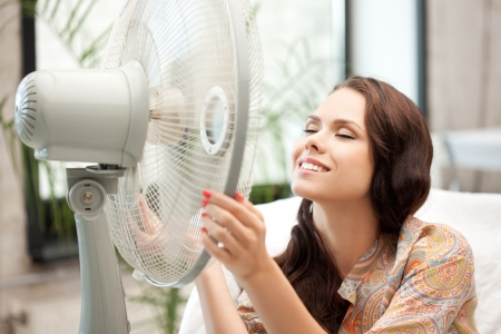 ventilator: picture of happy woman with big fan Stock Photo