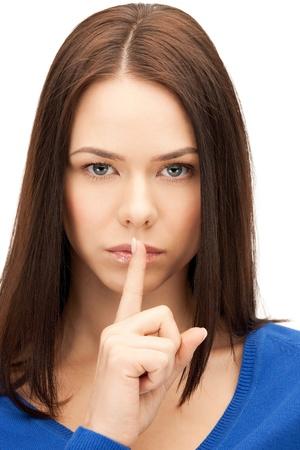 quiet adult: immagine luminosa di giovane donna con un dito sulle labbra.