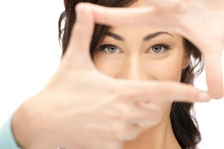 při pohledu na fotoaparát: obraz krásné ženy, vytváří rám s prsty