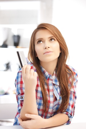 bright picture of pensive woman with credit card Stock Photo - 12178670