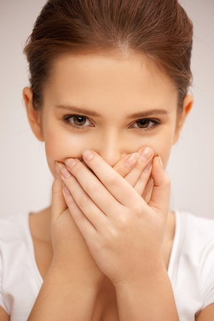 shh: bright closeup picture of woman with hand over mouth