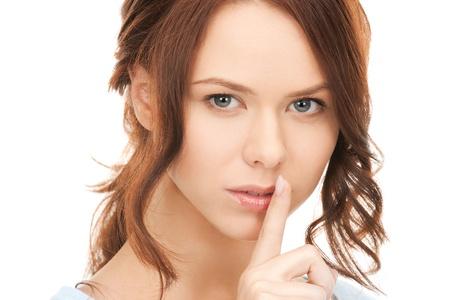 quiet adult: immagine luminosa di giovane donna con un dito sulle labbra