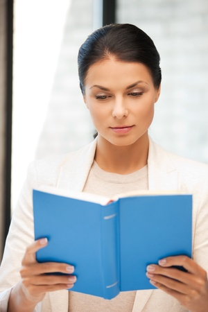 bright picture of calm and serious woman with book photo