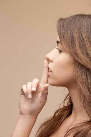 bright picture of young woman with finger on lips Stock Photo - 12382271