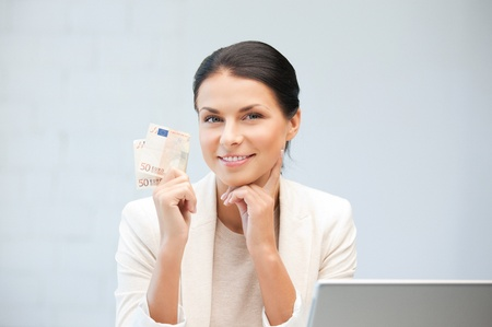 wages: picture of happy woman with laptop computer and euro cash money Stock Photo