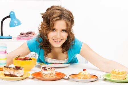 nice food: bright picture of lovely housewife at the kitchen sweets