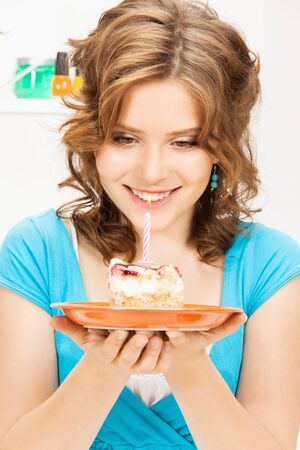 woman eating cake: bright picture of lovely housewife with cake and candle Stock Photo