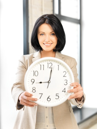 bright picture of attractive businesswoman with clock Stock Photo - 13582418