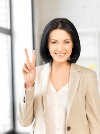 bright picture of young woman showing victory sign Stock Photo - 13772775