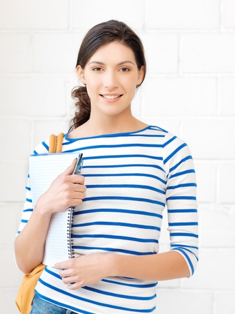 picture of happy and smiling teenage girl with big notepad photo
