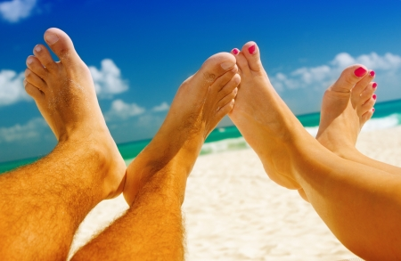 beach feet: picture of male and female legs over tropical beach background