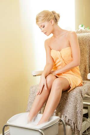 beautiful woman in spa salon having pedicure photo