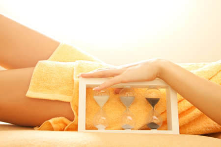 closeup picture of female hands and legs in spa salon with a sandglass photo