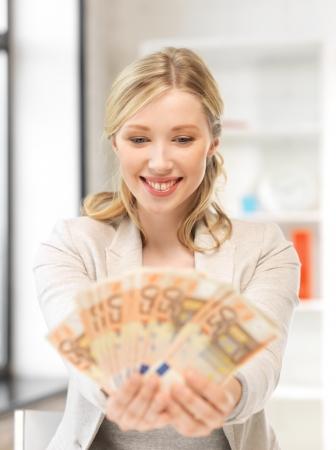 earn: brillante imagen de mujer hermosa con dinero efectivo en euros Foto de archivo