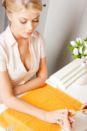 nailcare: attractive woman having a manicure at the salon