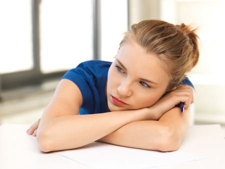 frustration girl: picture of tired teenage girl with pen and paper Stock Photo