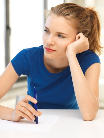picture of pensive teenage girl with pen and paper photo