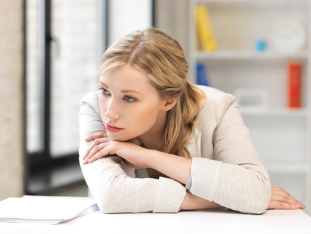 unhappy worker: bright picture of unhappy woman in office Stock Photo