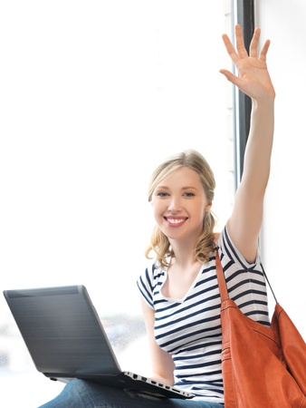 happy teenage girl waving a greeting with laptop Stock Photo - 14503989