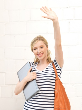happy teenage girl waving a greeting with laptop Stock Photo - 14538591